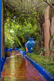 Garden scene with water. A pretty scenic garden with a water-filled moat or canal in Marrakech, Morocco Stock Photo