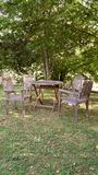 Garden scene. Wooden table and four wooden chairs set under trees Royalty Free Stock Images