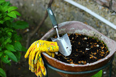 Garden Scoop and Garden Gloves in Flower Pot. Garden Scoop with Yellow Garden Glowes in Flower Pot with Brick Wall Behind Royalty Free Stock Photos