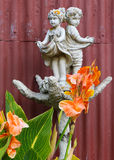 Garden Sculpture. Sculpture of the children with a wonderful bright orange flowers in the forground Royalty Free Stock Photography