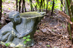 Garden sculpture birdbath. A rustic garden sculpture with birdbath featuring a young boy Royalty Free Stock Photos