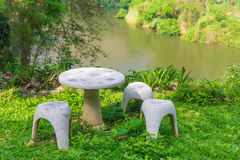 Garden seat of stone or stone table and benches  in the garden. Royalty Free Stock Photo