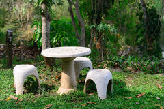 Garden seat of stone or stone table and benches  in the garden. Royalty Free Stock Images