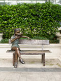Garden seating bench. With small girl statue Royalty Free Stock Photo