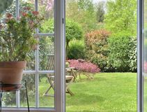 Window opening on ornamental garden. Garden seen by the inside of a house through a door makes windows opened Royalty Free Stock Photo