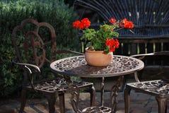 Garden set. With iron furniture and geranium pot Royalty Free Stock Photos
