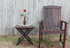 Garden setting. Dark wooden table and chair with red rose in sea glass bottle Royalty Free Stock Photos
