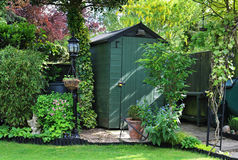 Garden Shed in an english back garden. English back garden with shed amongst the plants Royalty Free Stock Photography