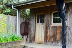An old garden shed or little house, aged and weathered, with some garden tools left next to it. Garden shed, garden house, old shed, old garden tools, gardening stock images