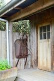 An old garden shed or little house, aged and weathered, with some garden tools left next to it. Garden shed, garden house, old shed, old garden tools, gardening royalty free stock photo