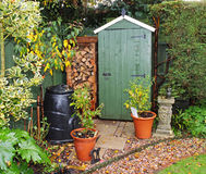 Garden Shed with log store. English back garden in Autumn with shed and log store Royalty Free Stock Photo