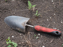 Garden shovel on ground. Photography of a garden shovel positioned on dark rich soil. Raw file format is also available for this photo Stock Image