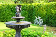 Garden with small fountain and stone bench green lawn plants trees. Shrubs royalty free stock photos
