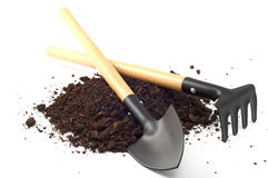 Garden spade and a rake on peat soil separately on a white backg Stock Photo