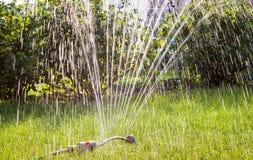 Garden sprinkler grass watering. Garden sprinkler on sunny summer day watering green fresh grass stock images