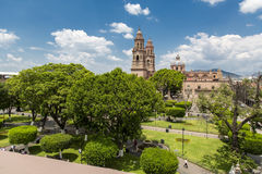 Garden of the square of morelia. Garden of the plaza de morelia in the background domes of the cathedral Royalty Free Stock Photos