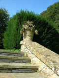 Garden stairway. Ornate garden steps flanked by low wall with stone carving of fruit basket at the top Royalty Free Stock Photo