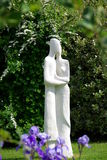 Garden Statue. A modern statue of the joined figures of a man and a woman in a pretty English country garden stock image