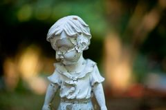 Garden statue of child in corroded condition. stock photo