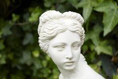 Garden statue close. Closeup of a small garden statue of a woman royalty free stock photography