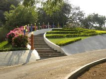 Hyderabad, India - January 1, 2009 Garden with steps, pink and red flowers, green grass, plants and trees at Ramoji Film City. Garden with steps, pink and red stock images