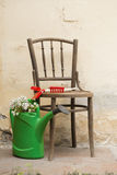 Garden still life with chair, garden tools and watering can Royalty Free Stock Photography