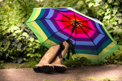 Garden still life. With water can, gum boots, and multicolored umbrella Royalty Free Stock Image