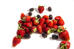 A lot of fresh sweet red strawberry`s with some blackberry`s. The garden strawberry or simply strawberry; Fragaria × ananassa is a widely grown hybrid species Stock Photos