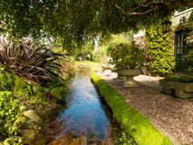 Garden Stream. This is a small section of a village stream which runs along the front of a number of old houses. It runs alongside the road, and each house is Royalty Free Stock Image