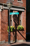 Garden street. Sign in bright sun light hangs from gas lamp post above two flower boxes with blooming flowers in beacon hill area of boston massachusetts Stock Photos