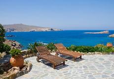 Garden with sun loungers. On the background of the sea. Mykonos. Greece royalty free stock photos
