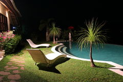 Garden with sun loungers and swimming pool at night. Vacation house, villa. Bali, Indonesia. Garden with sun loungers, palms and swimming pool at night royalty free stock photo