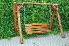 Garden swing. Wooden swing against a wall overgrown green vegetation Stock Image