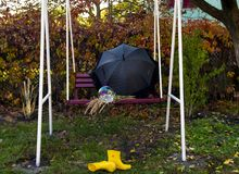 Garden swing with a large umbrella and a bouquet of wild flowers forgotten after the rain, royalty free stock photo