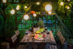 Garden table with appetizers and wine in summer evening. On old wooden table royalty free stock photography
