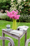 Garden table with book, paper, drinks Stock Images