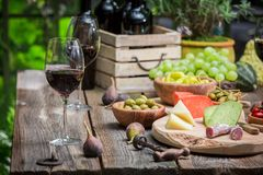 Garden table with cheese, red wine in the evening. Session in outside royalty free stock images