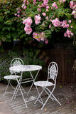 Garden table with roses. Pink climbing rose on a pergola behind a white wrought iron garden table and two chairs perfect for alfresco dining Stock Images