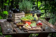 Garden table with snacks, wine and fruits in the evening. On old wooden table stock image