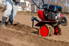 Garden tiller to work, closeup. Man working in the garden with Garden Tiller. Garden tiller to work, closeup. Man with tractor cultivating field at spring stock photos