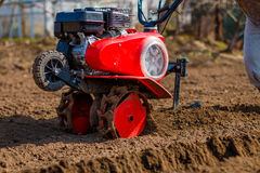 Garden tiller to work. Man working in the garden with Garden Tiller. Garden tiller to work, closeup. Man with tractor cultivating field at spring stock image