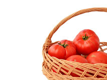 Garden tomatoes in a wicker basket isolated Stock Image