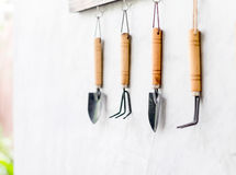 Garden tool hanging on concrete wall with wooden label Royalty Free Stock Photos