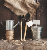 Garden tool, shovel, rake, watering can, bucket, bag on a wooden Stock Images