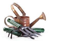 Garden tools. Copper watering can, fork, shovel, rake on a white background Royalty Free Stock Photo