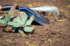 Garden tools. (cultivator, shovel, rake) over brown soil (ploughed land) close up. Copy space. Agriculture, gardening, soil cultivation concept Stock Photo