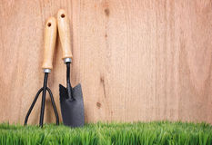 Garden tools and fork on green grass with wood Stock Photography