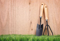 Garden tools and fork on green grass with wood Stock Photos