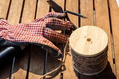 Garden tools with gloves, rake and cord on a table Stock Image