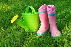Garden tools green grass background. Garden tools on green grass background, water can and pink rubber boots of a little farmer Royalty Free Stock Photos